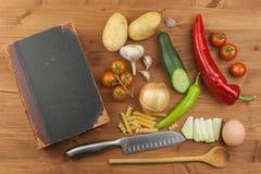 Vecchie ricette del libro di cucina su una tavola di legno Verdura sana del cuoco Preparazione dell'alimento domestico di dieta fotografie stock libere da diritti