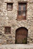 Vecchie rocce e pietre della costruzione maded Porta di legno e finestre curvate Immagini Stock