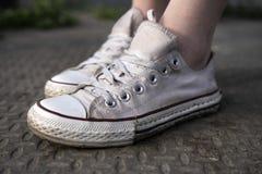 Vecchie scarpe da tennis bianche sulla via Immagine Stock