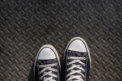 Vecchie scarpe da tennis blu scuro sulla via Fotografie Stock