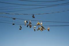 Vecchie scarpe da tennis indossate che appendono sui cavi di telefono Immagini Stock Libere da Diritti