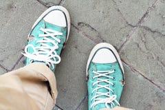 Vecchie scarpe da tennis verdi sul fondo della strada Fotografie Stock