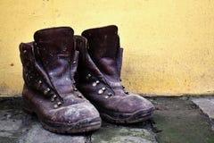 Vecchie scarpe di cuoio su fondamento del mattone e parete gialla nel fondo fotografia stock libera da diritti