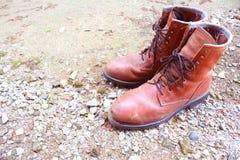 Vecchie scarpe di cuoio sulla terra fotografia stock libera da diritti