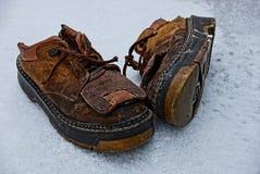 Vecchie scarpe marroni nella neve nell'iarda immagini stock libere da diritti