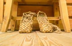 Vecchie scarpe russe della rafia sul pavimento di legno Fotografia Stock