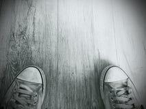 Vecchie scarpe su un pavimento di legno Fotografia Stock