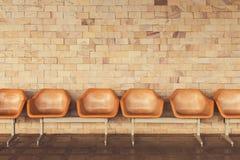 Vecchie sedie con il fondo giallo del muro di mattoni Immagini Stock