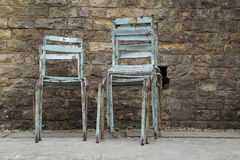 Vecchie sedie impilate del metallo contro il muro di mattoni di lerciume Fotografie Stock