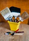 Vecchie spazzole in un vaso giallo Fotografie Stock