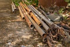 Vecchie tubature dell'acqua d'annata del PVC su terra concreta - giardino all'aperto fotografie stock