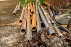 Vecchie tubature dell'acqua d'annata del PVC su terra e sulle pietre concrete - Outd immagini stock