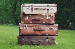 Vecchie valigie marroni alla moda sul giardino Immagini Stock