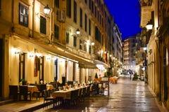 Vecchie vie della città della città di Corfù alla notte con i ristoranti Immagine Stock