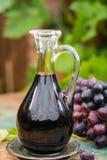 Vecchio aceto balsamico nero in una brocca di vetro con l'uva rossa fresca Fotografie Stock