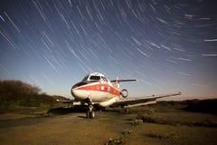 Vecchio aeroplano alla notte con le tracce della stella Fotografie Stock Libere da Diritti