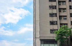 Vecchio angolo d'annata della costruzione di appartamento del brownstone con il fondo del cielo blu fotografia stock libera da diritti