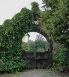 Vecchio arco di pietra con i portoni di legno fotografia stock