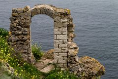 Vecchio arco fatto dei fiori selvaggi di pietra e gialli vicino al mare Immagine Stock