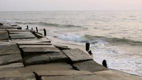 Vecchio argine di calcestruzzo distrutto con le colonne di legno che sporgono dall'acqua contro lo sfondo delle onde di oceano ne archivi video