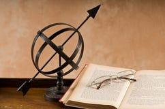 Vecchio armillare e libro. fotografia stock libera da diritti