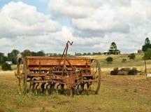 Vecchio attrezzo dell'aratro delle attrezzature agricole con il cielo nuvoloso Fotografia Stock