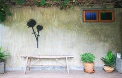 Vecchio banco di legno su un fondo di legno, su un giardino concreto e decorativo lucidato Immagini Stock Libere da Diritti