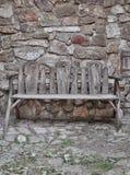 Vecchio banco di legno sulla casa di pietra fotografie stock