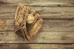 Vecchio baseball e guanto mezzo su fondo di legno approssimativo Immagine Stock