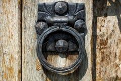 Vecchio battitore di porta del metallo nella forma del cerchio sulla porta di legno fotografie stock