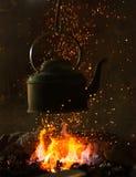 Vecchio bollitore del ferro sul fuoco fotografia stock