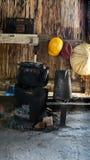 Vecchio bollitore nero sulla seduta sulla stufa vecchia piccola della legna da ardere Immagine Stock