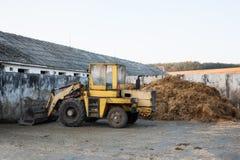 Vecchio bulldozer vicino al mucchio di concime Immagine Stock