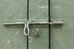 Vecchio bullone del ferro alla porta di legno verde Fotografia Stock