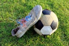 Vecchio calcio e vecchia scarpa sull'erba Fotografia Stock