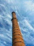 Vecchio camino industriale del mattone su cielo blu Fotografia Stock