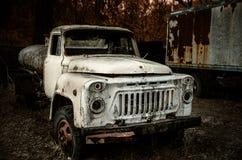 Vecchio camion arrugginito abbandonato al nel legno Fotografia Stock