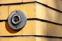 Vecchio campanello metallico scuro sul muro di mattoni fotografia stock
