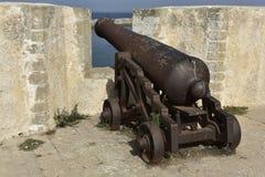 Vecchio cannone arrugginito dietro le grandi pareti immagini stock libere da diritti