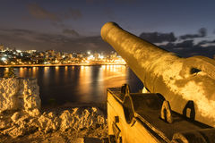 Vecchio cannone bronzeo che punta su vecchia Avana da una fortezza storica Immagine Stock