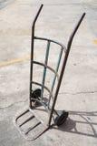 Vecchio carrello a mano del metallo vuoto sul pavimento del cemento Immagine Stock Libera da Diritti
