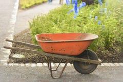 Vecchio carretto arrugginito della carriola nel giardino Funzionando nel giardino immagine stock libera da diritti