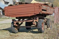 Vecchio carretto tagliato rosso del rimorchio di trattore situato sul coun del villaggio Fotografia Stock