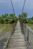 Vecchio cavo d'acciaio e passerella di legno attraverso il fiume Ponte sospeso di legno Fotografia Stock