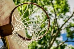 Vecchio cerchio di pallacanestro contro un fondo degli alberi immagine stock