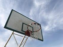 Vecchio cerchio di pallacanestro nell'ambito della vista con il fondo del cielo blu fotografie stock libere da diritti