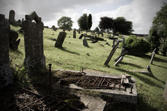 Vecchio cimitero con le pietre tombali piegate Immagine Stock