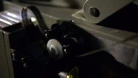 Vecchio cineproiettore che gioca nella notte Primo piano di una bobina con un film archivi video