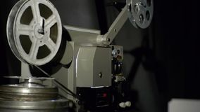 Vecchio cineproiettore che gioca nella notte Primo piano di una bobina con un film Il film ha esaurito il film stock footage