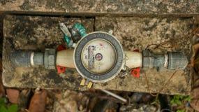 Vecchio contatore per acqua bianco d'annata sulla pietra concreta sporca in GA immagine stock libera da diritti